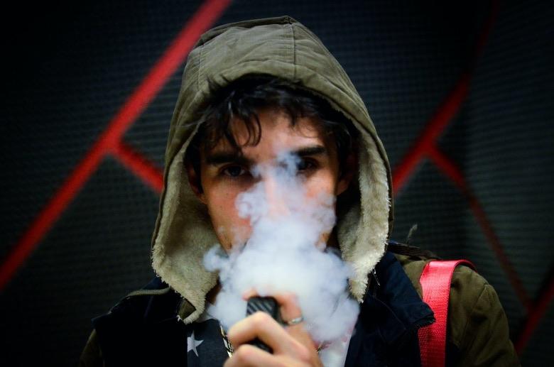 uomo che vaporizza liquidi per sigaretta elettronica