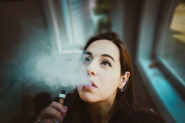 ragazza che usa la sigaretta elettronica per tiro di guancia