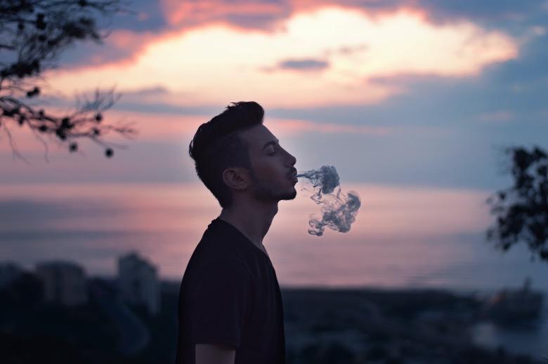 Ragazzo che fuma e-cig distante dai bambini