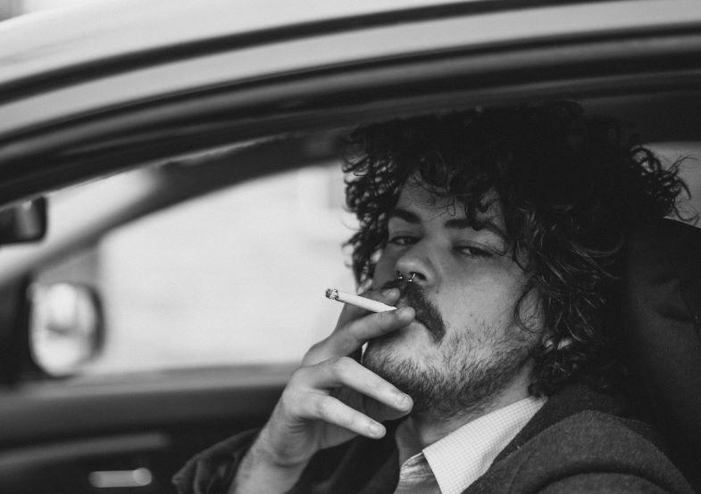 Si può fumare in macchina da soli? Ragazzo che fuma senza passeggeri.