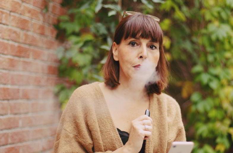 donna che utilizza una e-cigarette a guancia