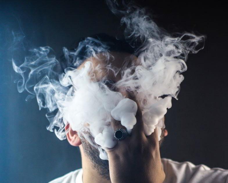 ragazzo che espira il vapore di una sigaretta elettronica polmonare